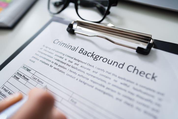 Hand Filling Criminal Background Check Application Form